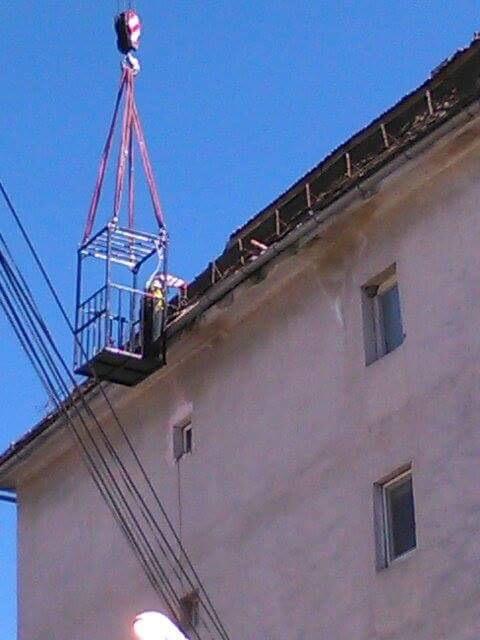 Beclenarii își repară acoperișurile blocurilor cu ajutorul unei macarale pusă la dispoziție de Primăria Beclean