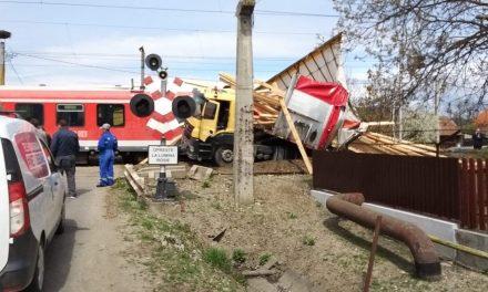 Accident feroviar la trecerea de cale ferată de pe drumul Rușului! Un TIR care transporta lemne a fost lovit din plin de un tren personal. Două persoane din tren, rănite